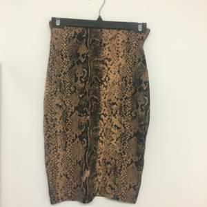 Ormönstrad kjol. Säljer tillhörande topp. Aldrig använd.