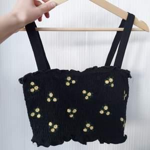 Ett svart linne med broderade blommor på. Är även croppat.