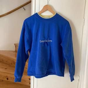 Jättesnygg blå vintage Calvin Klein sweatshirt. Gulnat lite över kragen och texten men inget annat slitage.