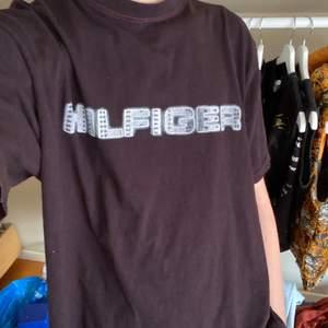Vintage Hilfiger t-shirt köpt på beyond retro 2017. Den är typ mörkbrun/burghundy/svart med röda sömmar. Trycket är sprucket men sitter kvar! Fint vintage skick! Står strl. M men sitter större, skulle säga L/XL, jag på bilden är 190🤎