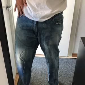 Blekta Jeans, bra skick i storlek 42/30, med egengjord slitning där nere vid fötterna