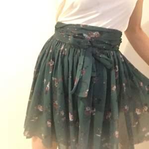 Grön Georgette kjol med blommig mönster och lång skarp för knyta i midjan från GANNI. Modellen heter Olive.