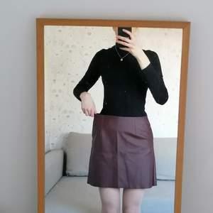 Mörkbrun kjol i läderimitation med två djupa fickor. Storlek M men passar M eller L. Prislappen sitter fortfarande kvar.