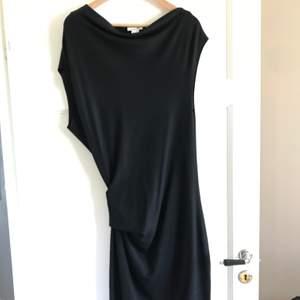 Asymmetrisk halvtight knälång klänning i lätt stretchigt tyg från Helmut Lang. Perfekt LBD! Aldrig använd o säljs pga fel stl.