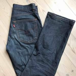 Snygga mörka jeans från trendiga Levi's. Högmidjade och raka/liten bootcut. Knappt använda och ganska stretchiga i materialet. Storlek 28/30😊