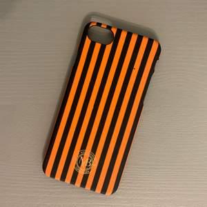 Orange- och svartrandigt skal från By Malene Birger för iPhone 7. Fint skick, förutom att den orange färgen har försvunnit på små små ställen. Kan skickas om köpare står för frakt! 🥰