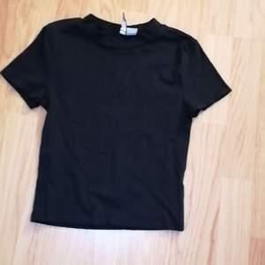 Basic svart t-shirt från h&m. Andvänt ca 3ggr så den är i nyskick. Tröjan är även lite croppad och sitter tajt. S nen passar kanske xs också🥰