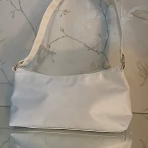 Vit baguette väska i tyg, som har guld detaljer.