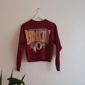 Sweatshirt med NFL-tryck. Bra skick, lite nopprig. Gissar på att den är i storlek S. Croppad modell. Frakt tillkommer.