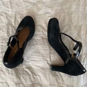 Söta klackskor från Clarks i svart samett med ett spänne i mitten. Snygga till jeans eller stay-ups och klänning till. Bra skick, använt vid fåtal tillfällen.