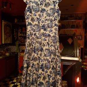 En fin klänning beige /vitmed blåa blommor på i storlek S. Frakt 66 kr spårbart