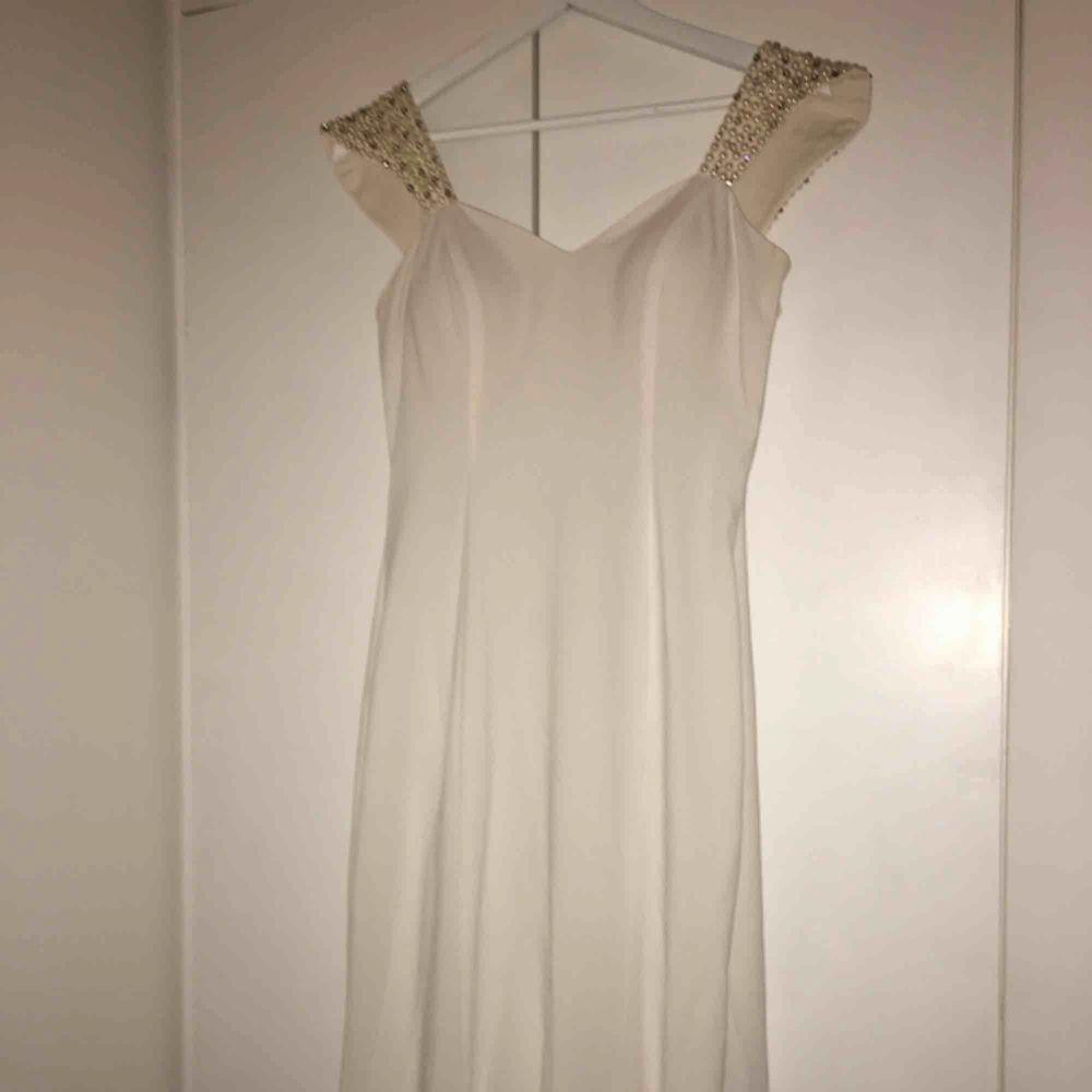 En helt oanvänd vit fest klänning med fina detaljer på baksidan med pärlor och en roset. Den är lång och har ett litet släpp i baksidan. Den är i perfelt skikt. Etiketten finns kvar. Skriv privat för fler bilder. Passar M och L. Pris kan diskuteras . Klänningar.