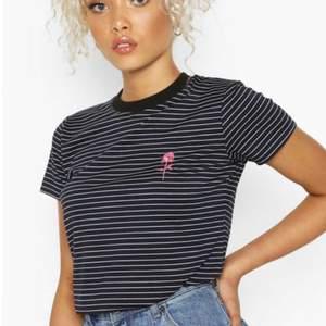 Randig T-shirt med rosa broderad blomma från Boohoo. Storlek S. Använd ca 3 ggr.  Frakt ingår i priset