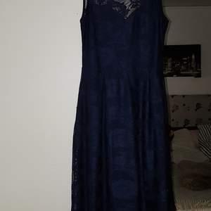 Mörkblå medellång klänning i blommigt spetstyg. Klänningen är i storlek 40 och är bra i storleken, inte för stor för att vara en 40. Jag har själv köpt den begagnad men den är i ett fint skick.