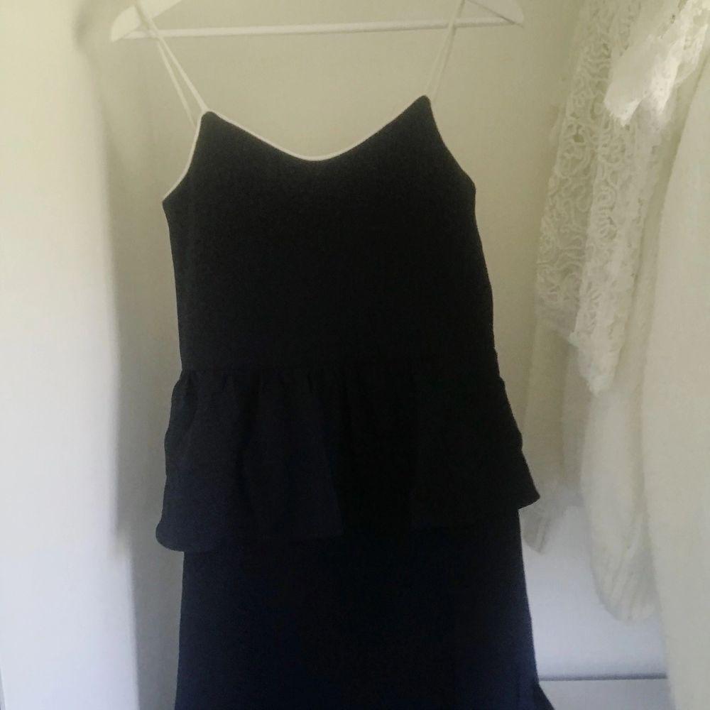 Helt nyinköpt mörkblå GANNI klänning med vita justerbara axelband. Storlek 36. Volanger vid midjan och två superfina slits. Går under knäna på mig som är 169cm. Säljer på grund av för stor på mig. Prislapp finns kvar, köpt för 139 euro. . Klänningar.
