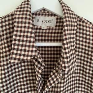 Rutig brun skjorta som passar som både skjorta och som en tunn jacka! Köpare står för frakt.