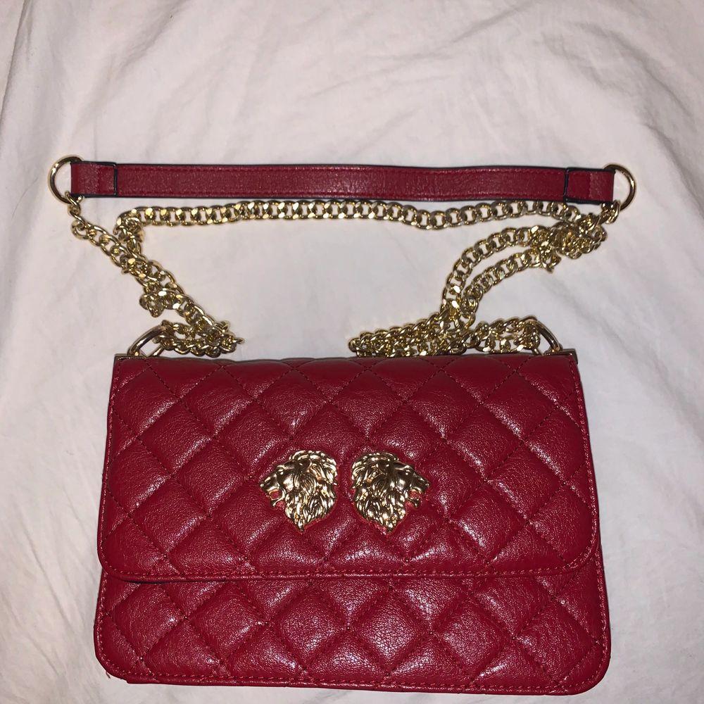En skit snygg röd väska med guldiga detaljer som jag köpt för ett tag sen och som inte kommit till användning en enda gång och är som i helt nytt skick❤️ den har inte nåt speciellt märke utan köpte den på bara nån väskbutik😁 köpte väskan för 500kr och säljer den för 300kr. Väskor.