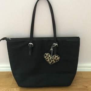 En svart väska med leopard inuti. Använd några fåtal gånger. Har tre fack inuti varav ett kan man stänga. Leopard-nyckelringen går att ta av. 49kr + frakt🖤