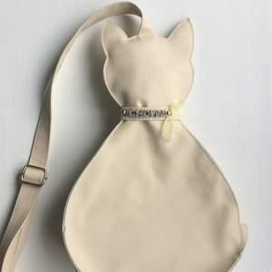Unik beige kattformad väska från Chopin. Längd 35 cm från huvud till svans 🐱 Material: polyester. Oanvänd!