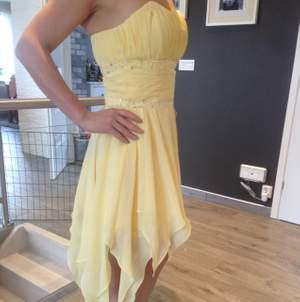 En jättefin, gul balklänning. Personen på bilden är 162cm, 170 cm med klackskorna.  Använd endast en gång så är i nyskick. Skräddarsydd i USA Passar perfekt till balen eller bröllop.  Kan skickas mot fraktkostnaden  Skickar gärna fler bilder