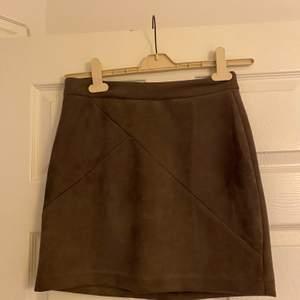 Grå/brun/nude kjol från DM retro. Aldrig använd. Blixtlås baksidan. Väldigt skön kvalite,mocka Fraktkostnad tillkommer.