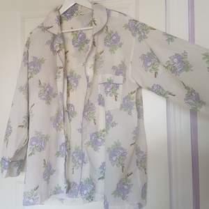 Jättesöt tunn krämvit nattskjorta med lila/blå blommor. Kan änev användas som vanlig blus/skjorta.
