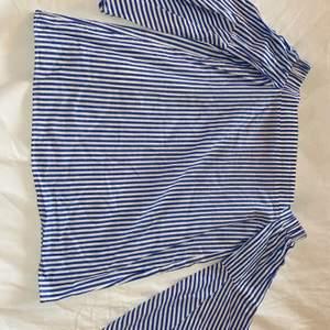 Blå- och vitrandig offshoulder blus med utsvängda armar.
