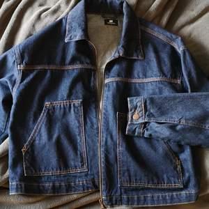 Jeansjacka i mörk jeansfärg. Två stora fickor. Riktigt skön och har unisexform på modellen.