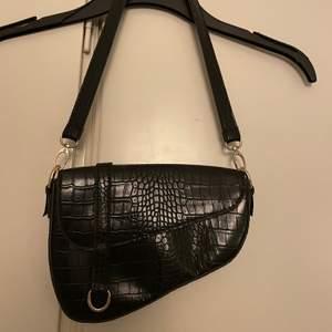 Fin sadle bag j svart fake ormskinn. Perfekt storlek, får plags med nycklar, mobil, plånka och kanske läppglans och en spegel.