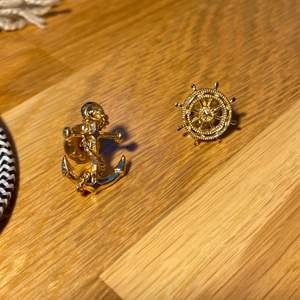 """Guldiga pins, ett ankare och en """"ratt"""". Köpta på H&M från några år sedan men har använts högst 1 gång. 10kr styck eller båda för 18:-) Köpare betalar frakt."""
