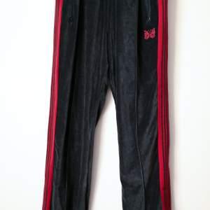 !Inte äkta! Men väldigt bra kvalite, 1:1 kopia.                            Needles trackpants i velour, rödsvarta, köpare står för frakt! INTRESSKOLL säljer vid bra bud                                  BUD: 350 kr