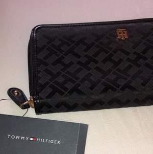 Oanvänd plånbok från Tommy Hilfiger. Fick den i present men hade redan liknande och säljer därför denna superfina plånbok! Prislappen sitter kvar och nypris är 900kr men denna är köpt på en outlet för $58 och säljer därför denna för 200kr! Frakt ca 50kr
