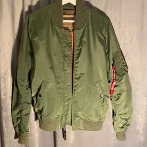 Klassisk bomberjacka från Alpha Industries i storlek S. Använd fåtal gånger och ser helt ny ut. Olivgrön färg och innerfoder i orange. 700 kr