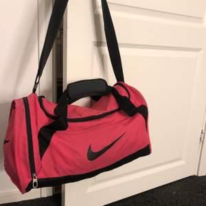 Rosa väska från nike. Väskan har många smidiga fack inuti. Använde väskan mycket när jag spelade fotboll eftersom den har ett fack på sidan perfekt för skor. Skickar gärna fler bilder om så önskas🥰 perfekt för gym, idrott, skolväska eller annan aktivitet:)