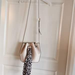 Helt ny oanvänd väska. Ljusbeige konstläder/skinn med leopard band. Så snygg men aldrig kommit till användning.