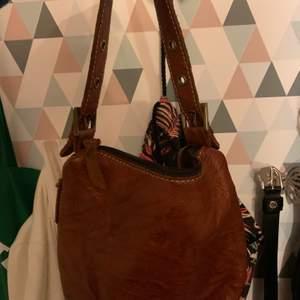 En liten brun väska, aldrig använd. Den är trevlig men som sagt får ingen användning för den. Har justerbart band och mycket plats med fickor på sidorna också👍🏼 (köparen står för frakten)