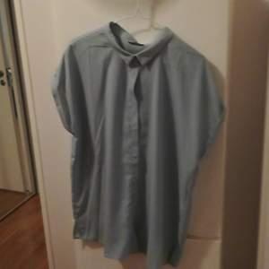 Lös, boxig blusskjorta med vikta korta ärmar och dolda knappar från Kiomi strl 42. Färgen är svår att beskriva, men närmast är nog mycket ljus grön/grå. Endast använd en gång, passar inte mig längre. Du står själv för fraktkostnad.