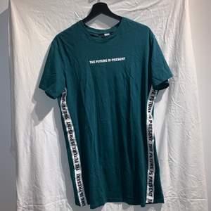 """Snygg grön T-shirt med texten """"the future is present"""" vid bröstet och längst sidorna. Jag älskar färgen på denna tröja men trots det används den inte och därför säljs den. Tröjan är i gott skick och är oversize"""