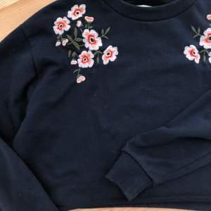Marinblå sweatshirt som är avklippt längst ner. (Har klippt själv). Fina broderade blommor!🌸 Säljer rätt så billigt då den är lite nopprig, se närbilden. Det står storlek L men jag har S och den passar mig bra, så det beror på hur man vill att den ska sitta💖