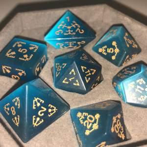 7 blå skimrande tärningar av halvädelstenar (blå kattöga) med guldiga siffror. Dem är som nya och har bara blivit använda ett fåtal gånger. (Kostade 800kr när vi köpte dem)
