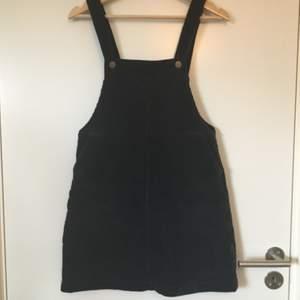 Mörkblå manchesterklänning med hängslen från Monki. Stl. XS. Gott skick, knappt använd. Frakt betalas av köparen.