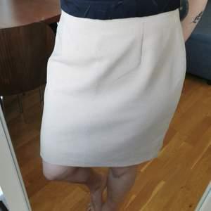 Beige/vit mini-hundtandsmönstrad kjol i strl C44, uppskattningsvis M/L. Måtten är midja 42 cm, höft 55 cm, längd 53 cm. Dragkedja bak. Köparen står för porto 55 kr.