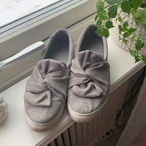 Gråa mocka skor.
