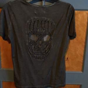 Helt ny oanvänd T-shirt som har blivit hängande i garderoben. På ryggen finns döskalle motivet o det är genombruten som syns på bild. Tröjan är gråmelerad. Köpare betalar frakt