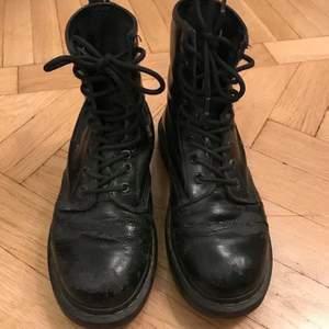 """Ett par Dr.Martens av den """"klassiska"""" modellen 1460 som är använda med en del sprickor i färgen i lädret samt ett litet hål/spricka jag tänkt limma, men köpte istället nya. Ett par lösa öljetter jag tänkt göra detsamma med. Annars i fint skick o h har mycket kvar att ge!  290:- inkl frakt eller mötas i Stockholm billigare! ✨❄️✨  Martin kängor boots martens drmartins drmartens vinterskor stövlar stövletter skor läder skinn vinter"""