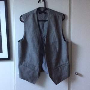 Fin oanvänd väst i strl XS, i herrmodell. Sitter snyggt casual på en XS upp till M, beroende på hur man vill att den ska sitta. Är själv 156 och den är lite oversize, men snyggt. Passar till enkel t-shirt eller skjorta och jeans, allroundplagg.