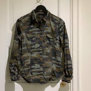 Snygg kamouflage mönstrad skjorta med detaljer i mässing. Fickor fram. Snygg dragkedja som detalj. Stl 38. Swish gäller. 📦 Möts / köpare står för frakt. Djurfritt & rökfritt hem.