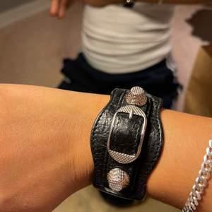 """Supersnyggt armband som samlar damm, med nitar från balenciaga deras """"black leather arena giant studed silver bracelet"""". Köpt på blocket för 1200kr. Storlek M men justerbar storlek (passa mig med små armleder) sparsamt använt. Lådan och lappar får man med."""