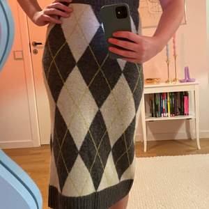 Så mysig och trendig rutig stickad kjol som slutar mitt på vaden. Slits baktill och resår i midjan.