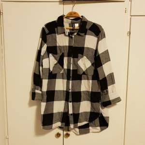 Rutig skjorta i svart/vitt/grått, bomull, mjuk o skön, lätt att knyta upp om man vill. Använd men hel o fin, köparen står för frakt :)